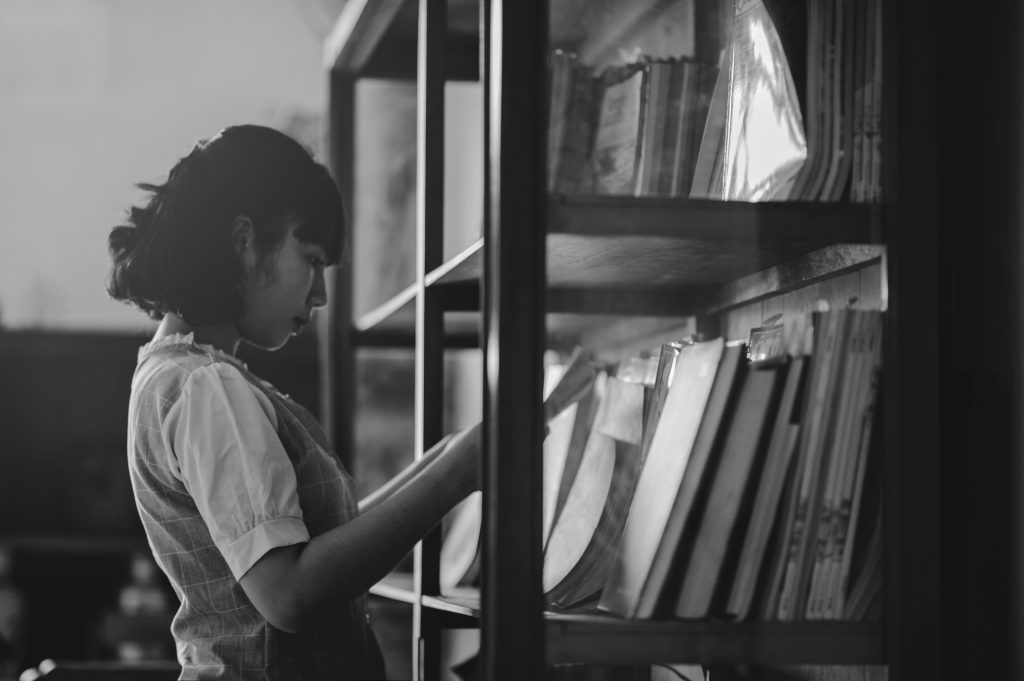 A woman looking through archival books on a shelf, trying to determine what her street looked like years ago