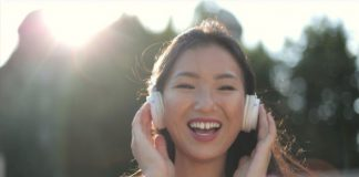 Smiling girl in red crew neck shirt with headphones