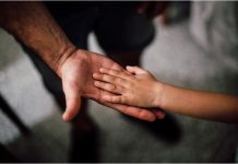 A small child's hand on an adults hand